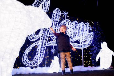 Little boy standing with the lighted sign and sculpture.